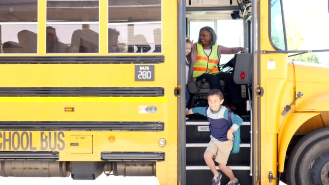 elementary school children unload bus - bus driver stock videos and b-roll footage