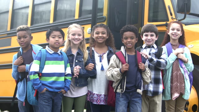 Elementary school children waiting outside bus video