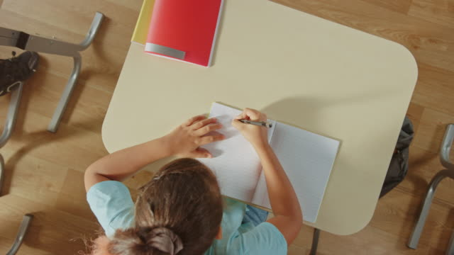 Elementary School Classroom: Girl Sitting at the  School Desk Working on Assignments in Exercise Notebooks. Zoom Out Top View Starting from the Exercise Book. Elementary School Classroom: Girl Sitting at the  School Desk Working on Assignments in Exercise Notebooks. Zoom Out Top View Starting from the Exercise Book. educational exam stock videos & royalty-free footage