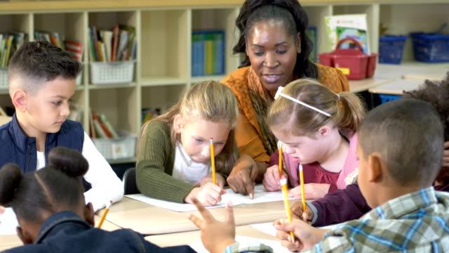vídeos de stock e filmes b-roll de elementary school classroom, girl with down syndrome - capacidades diferentes