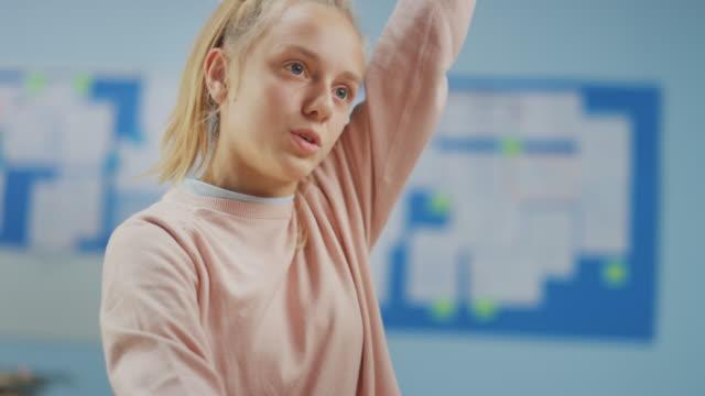 grundschulklassenzimmer: porträt eines niedlichen kleinen mädchens mit blonden haaren und pferdeschwanz hebenhand mit einer antwort. brillante junge studentstellte stellt frage. zeitlupe - grundschule stock-videos und b-roll-filmmaterial