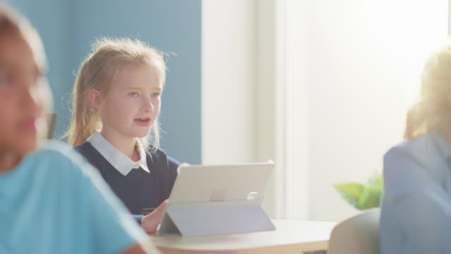 vidéos et rushes de elementary school computer science class: cute girl utilise digital tablet computer, soulève la main pour poser des questions. enfants obtenant l'éducation moderne dans stem, jeu et apprentissage. ralenti - professeur(e)
