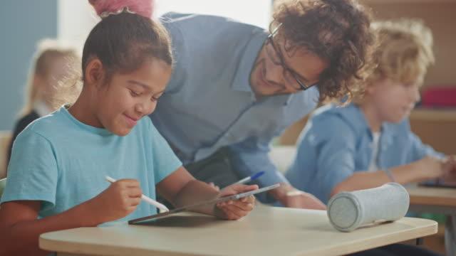 vidéos et rushes de elementary school computer science class: smart girl uses digital tablet computer, friendly teacher helps her by explaining leson and asignment. les enfants reçoivent une éducation moderne - professeur(e)