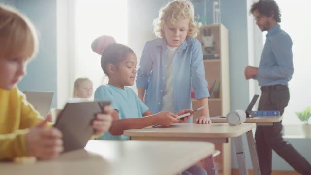 vidéos et rushes de elementary school computer science class: smart girl utilise digital tablet computer, son camarade de classe aide à l'affectation, ils font high five happily. les enfants reçoivent une éducation moderne - professeur(e)