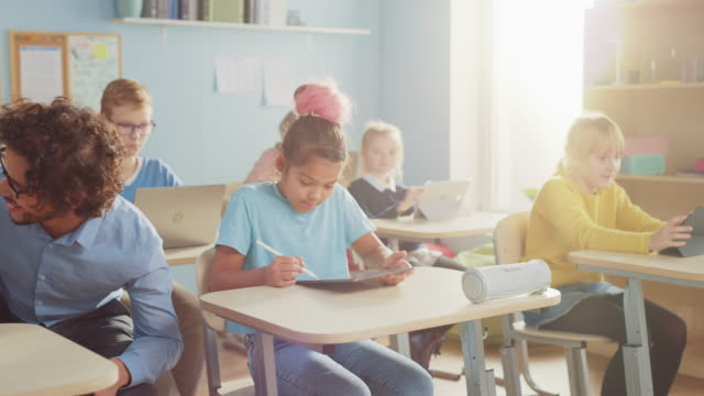 vidéos et rushes de elementary school computer science class: smart girl utilise digital tablet computer, ses camarades de classe travaillent avec des ordinateurs portables, l'enseignant amical se promène autour de la classe d'aider les enfants. les enfants reçoivent une é - professeur(e)
