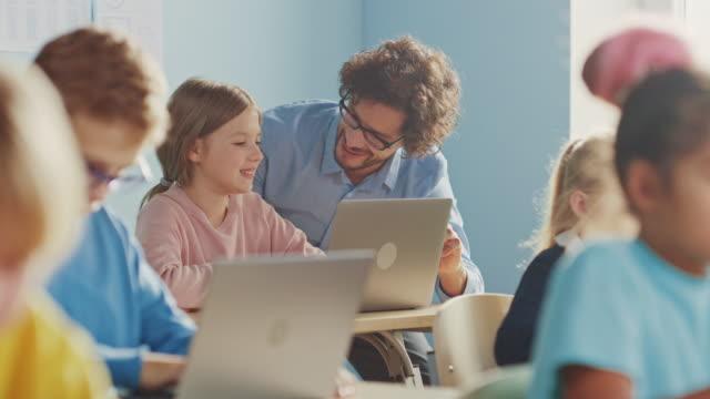 vidéos et rushes de elementary school computer science class: smart girl utilise ordinateur portable, professeur amical l'aide en expliquant la leçon et l'affichage. les enfants reçoivent une éducation moderne - professeur(e)