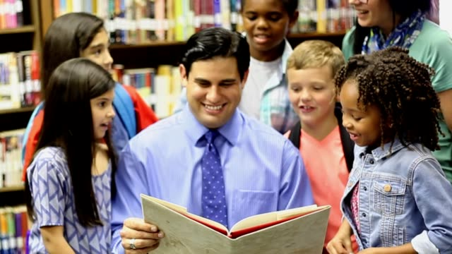Elementary school counselor with students in library. Latin descent, elementary school counselor meets with a multi-ethnic group of students in classroom or library to discuss current issues and enjoy a story. school counselor stock videos & royalty-free footage