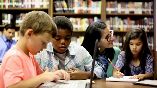 Elementary school counselor with students in library. Latin descent, elementary school counselor meets with a multi-ethnic group of students in classroom or library to discuss current issues. Students use computer, digital tablet and paper and pencil. school counselor stock videos & royalty-free footage