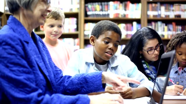 Elementary school counselor with students in library. video