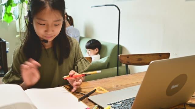 ホームリビングルームでビデオオンラインレッスンで勉強している小学生の女の子。 - 人里離れた点の映像素材/bロール