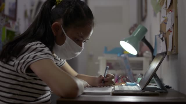 Elementary school girl wearing protective face mask and using digital tablet for lesson online at home.