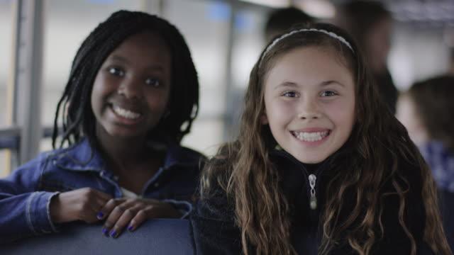 Escuela primaria niñas sonriendo mientras en autobús - vídeo