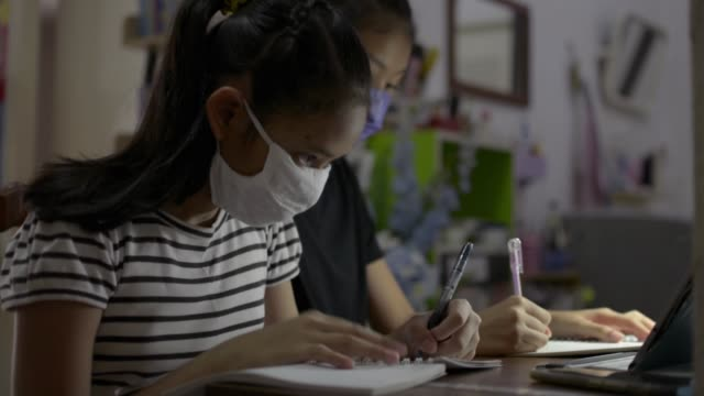 Elementary school girls wearing protective face mask and using digital tablet for lesson online at home.