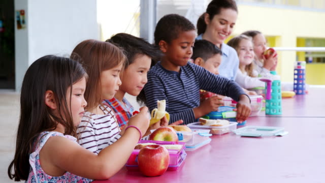 elementary school kids and teacher at a table eating lunch - scolaro video stock e b–roll