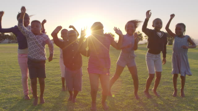 Elementary school kids jumping outdoors at sunset video