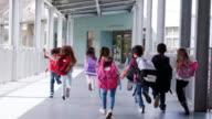 istock Elementary school kids run from camera in school corridor 1071486906
