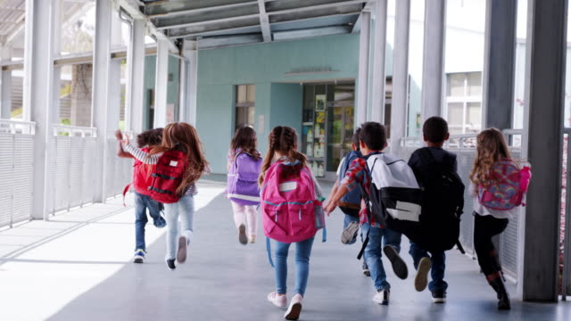 Elementary school kids run from camera in school corridor