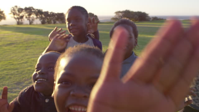 elementary school kids waving to camera outdoors, close up - bambine africa video stock e b–roll
