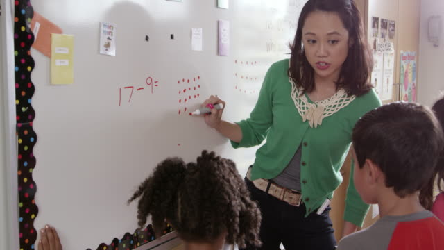 Elementary school math teacher works with kids at whiteboard video