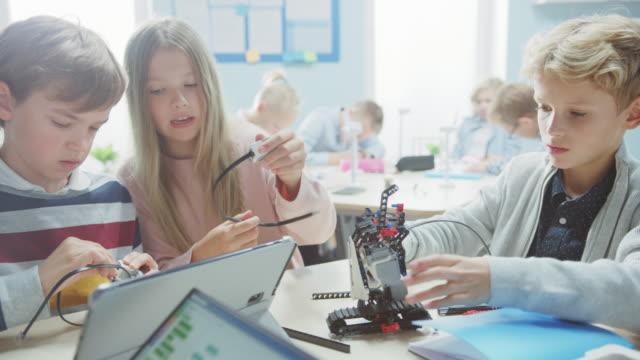 szkoła podstawowa robotics classroom: zróżnicowana grupa brilliant children building and programming robot, talking and working as a team. dzieci uczą się projektowania oprogramowania i kreatywnej inżynierii robotów - zagadnienia filmów i materiałów b-roll