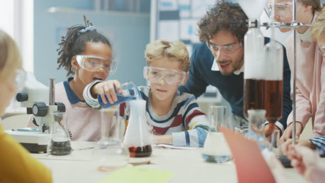 Elementary School Science Classroom: Enthusiastic Teacher Explains Chemistry to Diverse Group of Children, Little Boy Mixes Chemicals in Beakers. Children Learn with Interest video
