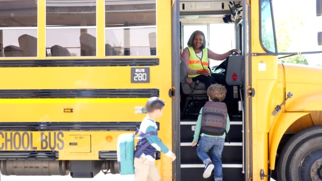 elementary school students board school bus after school - bus driver stock videos and b-roll footage