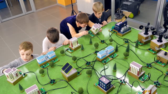 vídeos de stock e filmes b-roll de elementary school students doing study alternative energy project on a city prototype. - green city