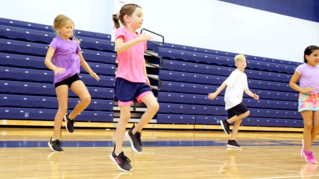 Elementary school students exercise during PE class Group of elementary school students run in place during PE class in the school gym. elementary age stock videos & royalty-free footage