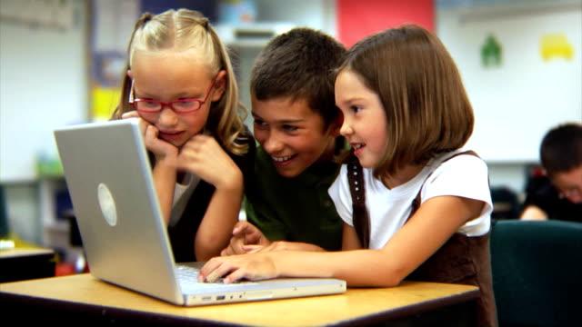 grundschule schüler suchen auf laptop-computer - grundschule stock-videos und b-roll-filmmaterial