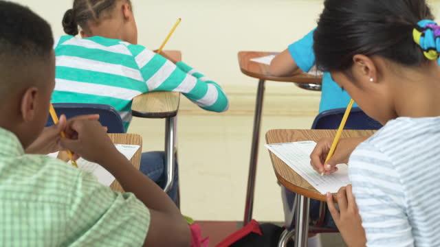 studenti delle scuole elementari che stanno facendo un test - piano americano video stock e b–roll
