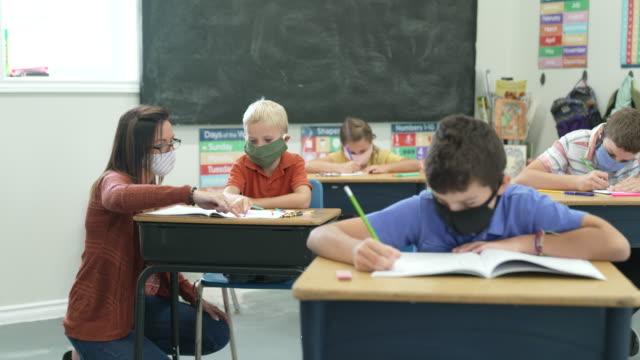 vídeos de stock, filmes e b-roll de alunos do ensino fundamental usando máscaras faciais protetoras na sala de aula - escola