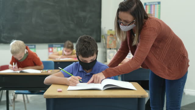 Video Elementary school students wearing protective face masks in the classroom