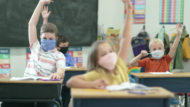 Elementary school students wearing protective face masks in the classroom Young students working at their desks in the classroom while wearing protective face masks to protect from the transfer of germs due to the COVID-19 outbreak. child stock videos & royalty-free footage