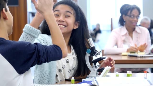 elementary school students working together on a science assignment - gestykulować filmów i materiałów b-roll