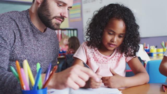 vídeos y material grabado en eventos de stock de profesor de la escuela primaria dando a la alumna de una a cada una de ellas de apoyo en el aula - consejero de la escuela