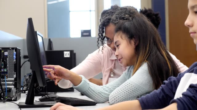 Elementary school volunteer tutors young girl in computer lab Mature female African American elementary school volunteer points to something on a computer monitor while helping a female elementary school student with an assignment. The student nods her head in understanding. stem research stock videos & royalty-free footage