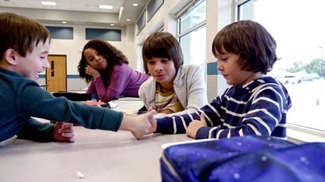 vídeos y material grabado en eventos de stock de los escolares de la escuela primaria luchan con el pulgar durante el almuerzo - escuela media