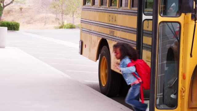 Elementary schoolchildren getting off school bus in morning Elementary schoolchildren getting off school bus in morning school buses stock videos & royalty-free footage