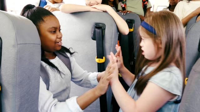 Elementary schoolgirl play clapping game on school bus video