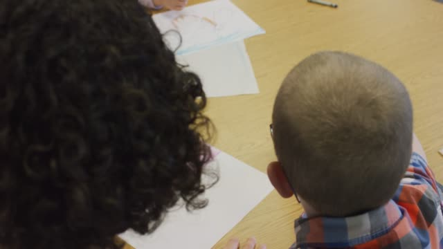 Elementary Students Coloring and Conversing video