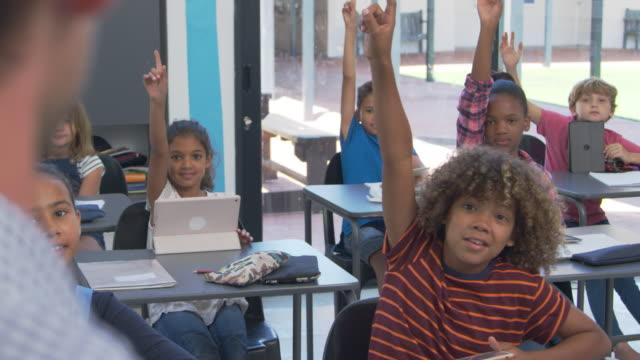 uczniowie szkół podstawowych szukają nauczyciela, przez widok na ramię - szkoła podstawowa filmów i materiałów b-roll