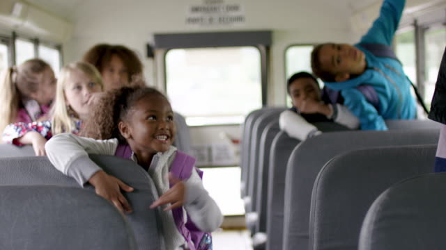 elementary students on the bus together - school buses stock videos and b-roll footage