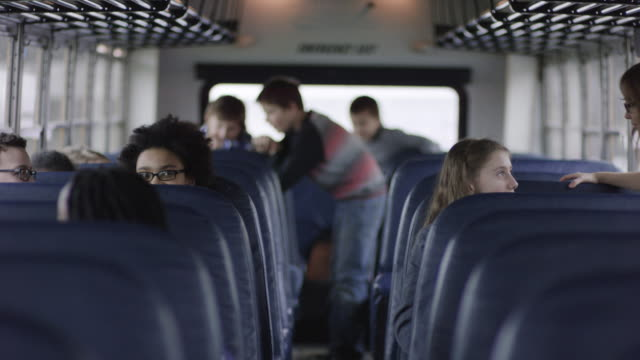 elementary students sitting inside school bus - school buses stock videos and b-roll footage