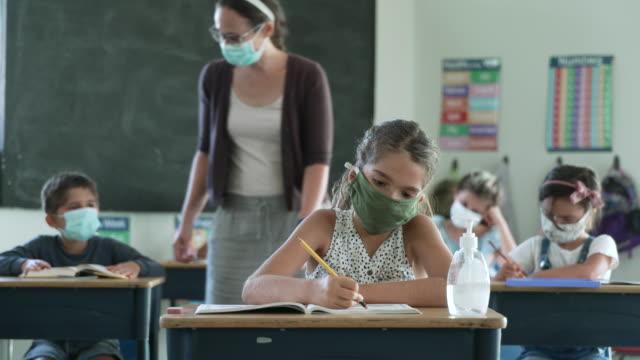grundschüler tragen masken im klassenzimmer - lehrkraft stock-videos und b-roll-filmmaterial