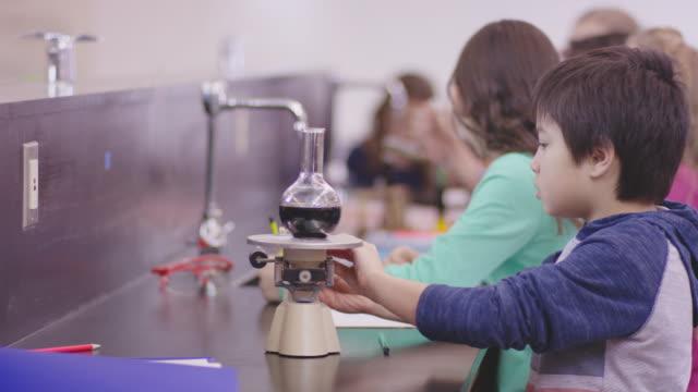 grundschulkind boy messung flüssigkeit in einer chemie-klasse - grundschule stock-videos und b-roll-filmmaterial