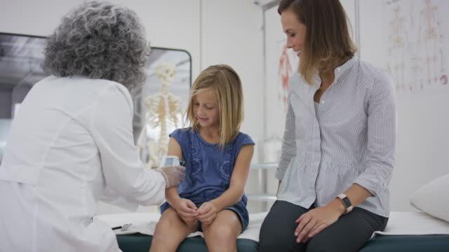 vídeos de stock, filmes e b-roll de ensino fundamental-idade garota senta-se sobre a mesa de exame enquanto o médico verifica a pressão arterial - vacina