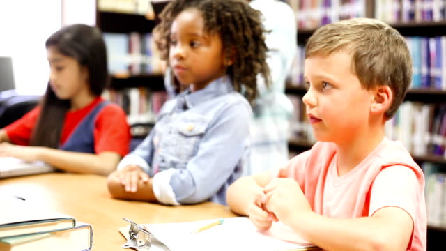 Crianças em idade escolar primária-idade trabalhando juntos e responder perguntas, levantando as mãos - vídeo