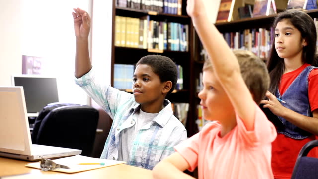 Elementary-age school children working together and answer questions by raising hands video