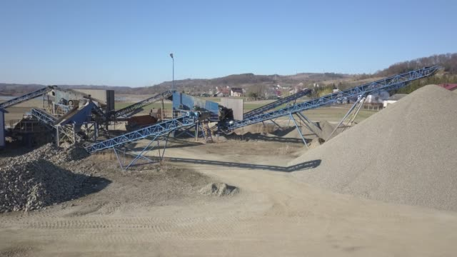 Elements of equipment for the extraction and sorting of rubble. Production of construction materials. Metal construction for working with stone and rocks. Slag of gravel under the conveyor belt construction vehicle stock videos & royalty-free footage
