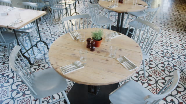 Elevated handheld view focussed on a round wooden table with place settings and chairs in an empty restaurant dining room, daytime